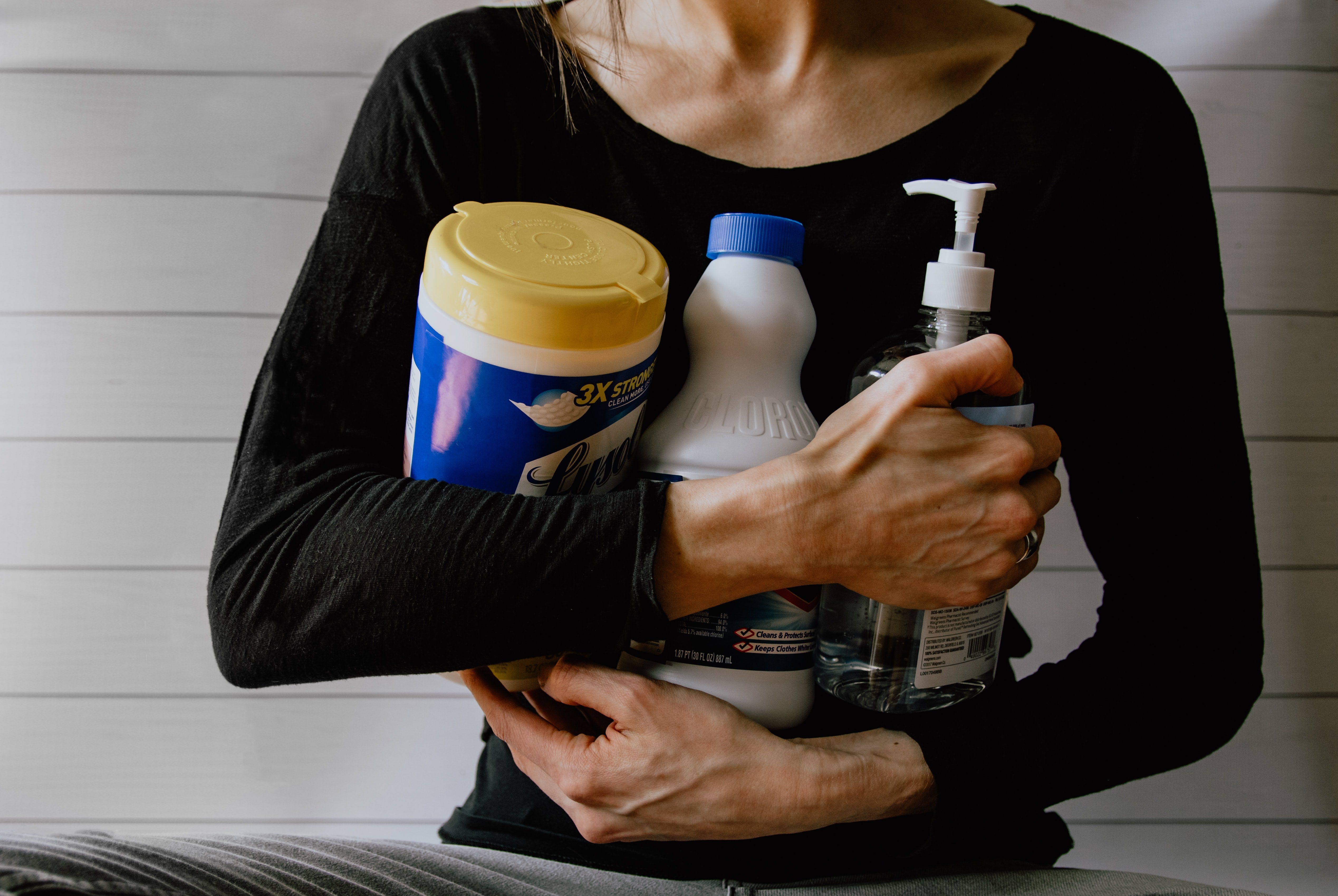 woman holding hydrogen peroxide to clean the bathroom in a shared house