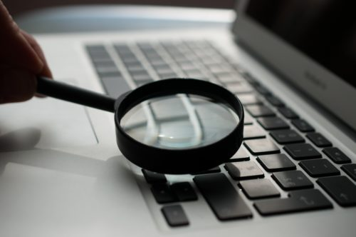 Magnifying glass searching on laptop for courses through ucas clearing 2021