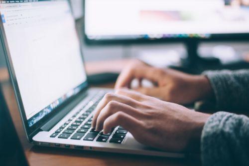 man typing on laptop excitedly