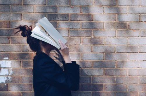 confused girl with book and brick wall